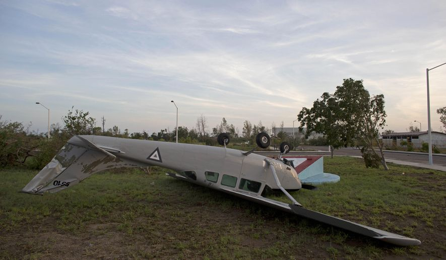 A Mexican air force aircraft lies overturned at the air force base in La Paz, Mexico, Wednesday, Sept. 17, 2014.  Mexico's government airlifted thousands of stranded foreign tourists out of the hurricane-ravaged resort of Los Cabos, as a weakened Odile headed over the Gulf of California Wednesday on a path toward Arizona and a new storm loomed to the south.(AP Photo/Dario Lopez-Mills)