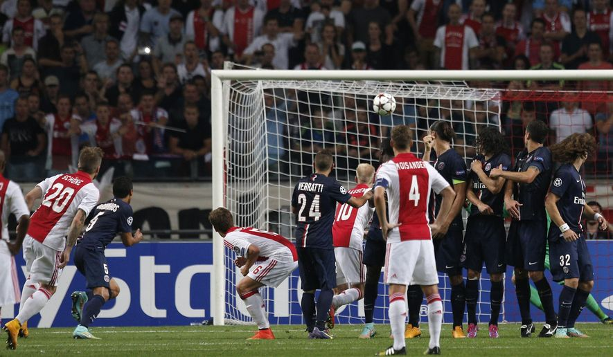 Ajax's Lasse Schone, left, shoots to score during the Group F Champions League match between Ajax and Paris Saint-Germain at ArenA stadium in Amsterdam, Netherlands, Wednesday, Sept. 17, 2014. (AP Photo/Peter Dejong)