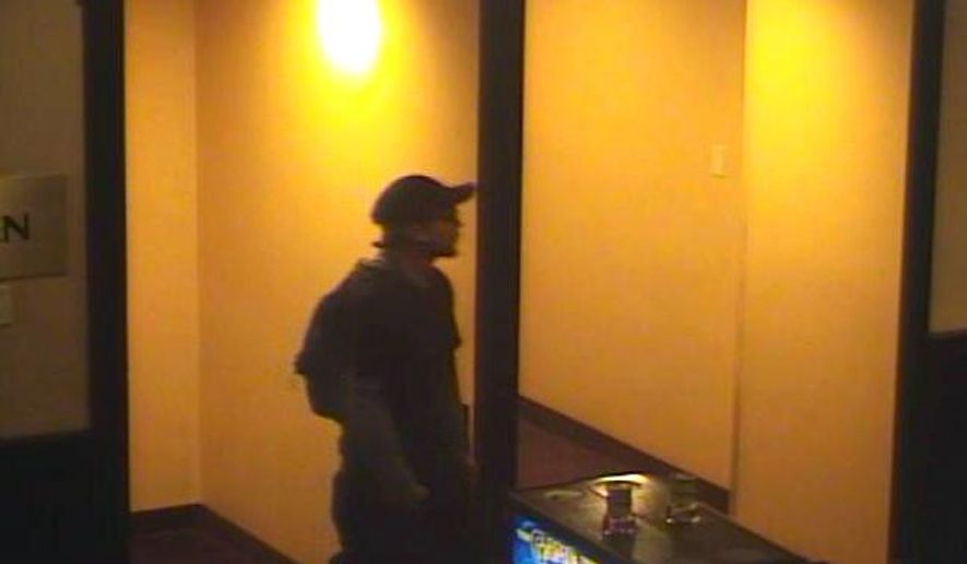 This undated video frame grab provided by Las Vegas Metropolitan Police Department, shows security video images of a man in his 20s or 30s who punched a sports book employee during a weekend heist at the Palace Station casino-hotel in Las Vegas. Witnesses reported seeing a weapon when the robber went behind a counter at the sports betting area on Sunday, Sept. 14, 2014. (AP Photo/Las Vegas Metropolitan Police Department)
