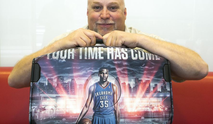 In this photo taken Tuesday, Sept. 16, 2014, 2K Sports Vice President Sports Development, Jeffrey Thomas, poses for a photo with his company's NBA 2K15 video game technology featuring NBA Oklahoma City Thunder Kevin Durant, during a demonstration at the Associated Press's office in Los Angeles. The NBA 2k15 upcoming basketball simulation video game developed by Visual Concepts and published by 2K Sports  releases Oct. 7, 2014. (AP Photo/Damian Dovarganes)