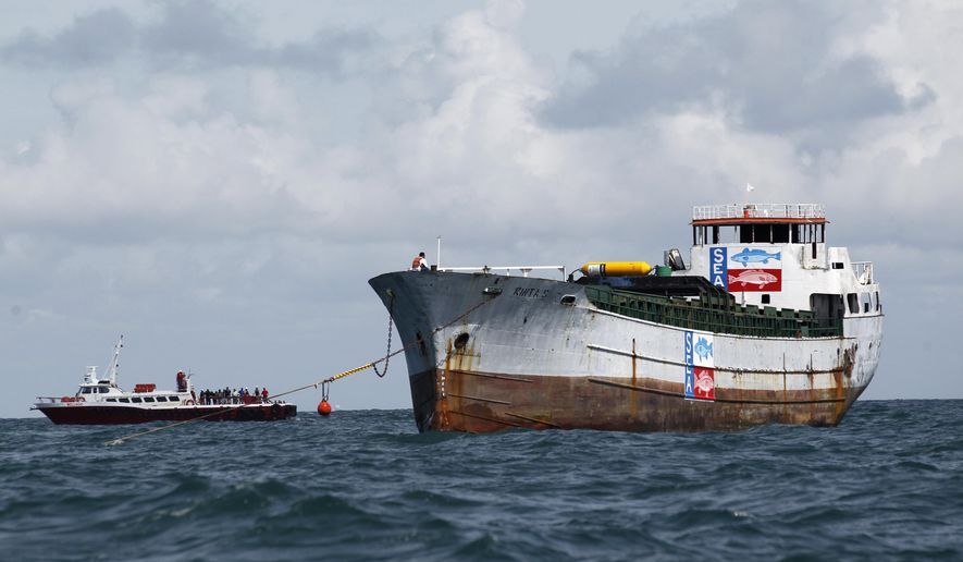 Onlookers wait from a nearby ship as the Kinta S cargo is positioned, Wednesday, Sept. 17, 2014 on the water to be sunk into the Gulf of Mexico to create an artificial reef off the Coast of Port Aransas, Texas. (AP Photo/Corpus Christi Caller-Times, Michael Zamora)