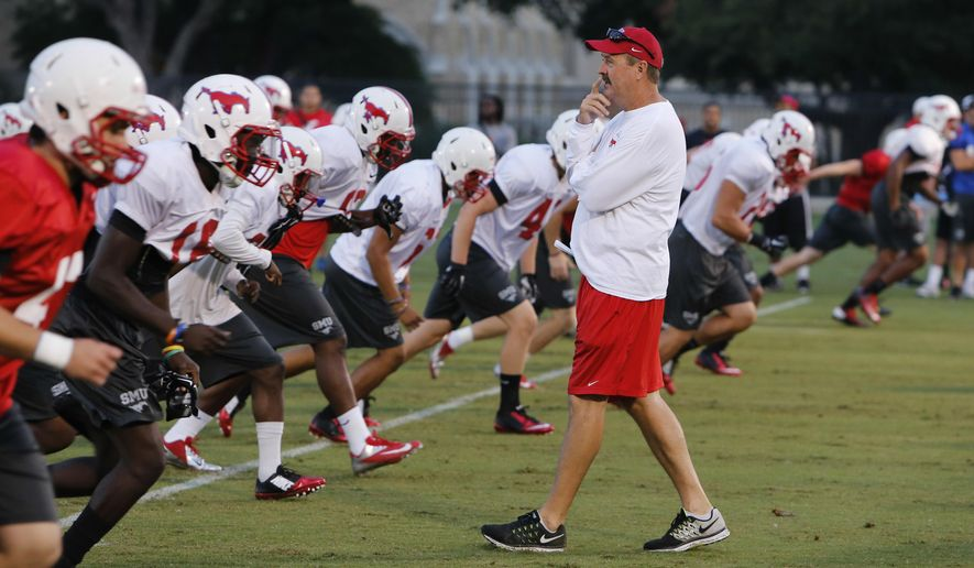 SMU interim football coach Tom Mason works with his team during NCAA college football practice Wednesday, Sept. 17, 2014, in Dallas. Coach June Jones resigned on Sept. 8, two days after SMU's only touchdown of the season was a long pass on the final play of a 43-6 loss at North Texas. SMU lost its opener 45-0 at seventh-ranked Baylor.   (AP Photo/The Dallas Morning News, David Woo)  MANDATORY CREDIT; MAGS OUT; TV OUT; INTERNET USE BY AP MEMBERS ONLY; NO SALES