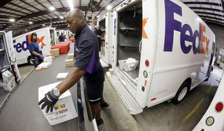 Mitchell Rodgers loads packages into his delivery truck at the FedEx Express station in Nashville, Tenn., in this July 9, 2014, file photo. FedEx Corp., on Wednesday, Sept. 17, 2014, reported profit of $606 million in its fiscal first quarter. (AP Photo/Mark Humphrey)