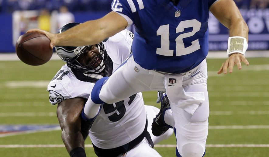 Indianapolis Colts quarterback Andrew Luck (12) is pushed out of bounds by Philadelphia Eagles defensive end Fletcher Cox (91) during the second half of an NFL football game Monday, Sept. 15, 2014, in Indianapolis. (AP Photo/Michael Conroy)