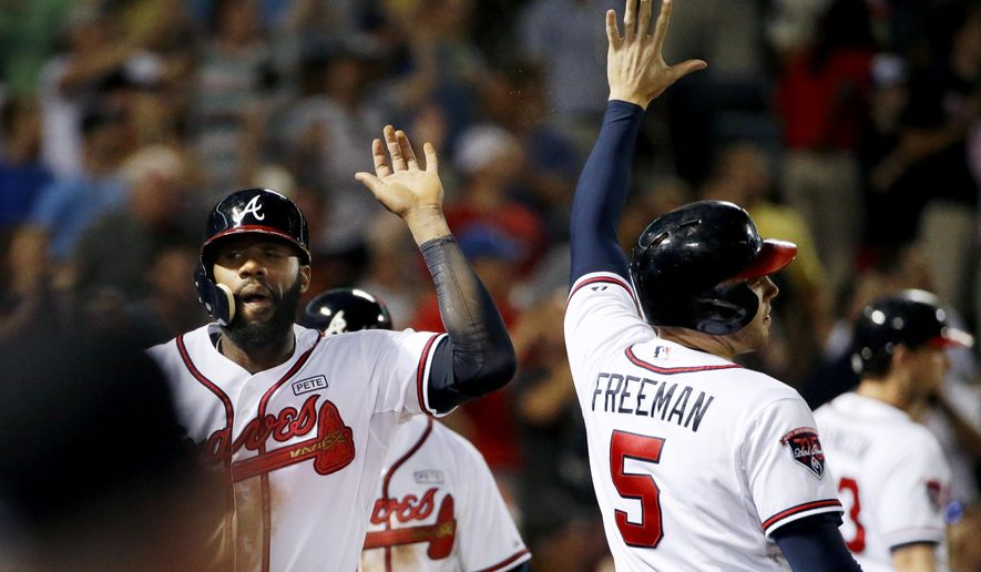 Atlanta Braves' Jason Heyward, left, high-fives teammate Freddie Freeman after they scored along with Phil Gosselin off a single by Christian Bethancourt in the sixth inning of a baseball game against the Washington Nationals, Wednesday, Sept. 17, 2014, in Atlanta. (AP Photo/David Goldman)