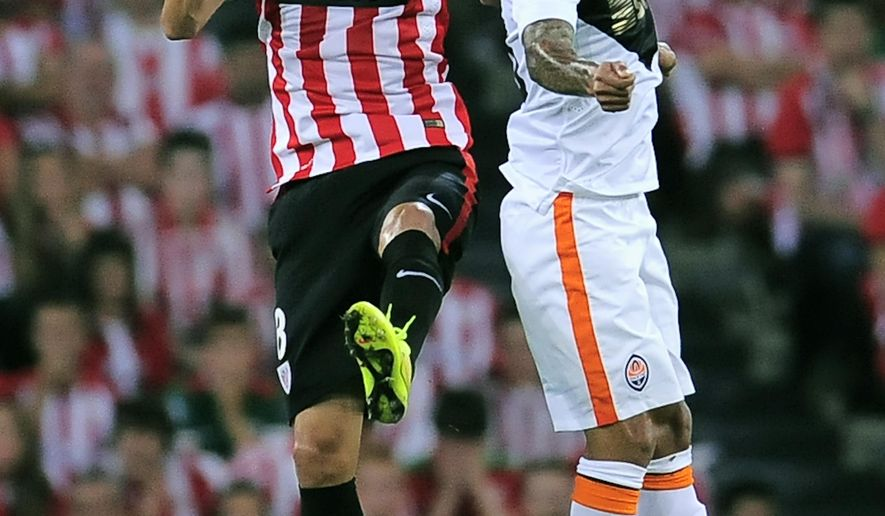 Athletic Bilbao's Ander Iturraspe, left, jumps for the ball with FC Shakhtar Donetsk's Alex Teixeira during the Champions League Group H soccer match between Athletic Bilbao and FC Shakhtar Donetsk at San Mames stadium, in Bilbao, northern Spain, Wednesday Sept. 17, 2014. (AP Photo/Alvaro Barrientos)