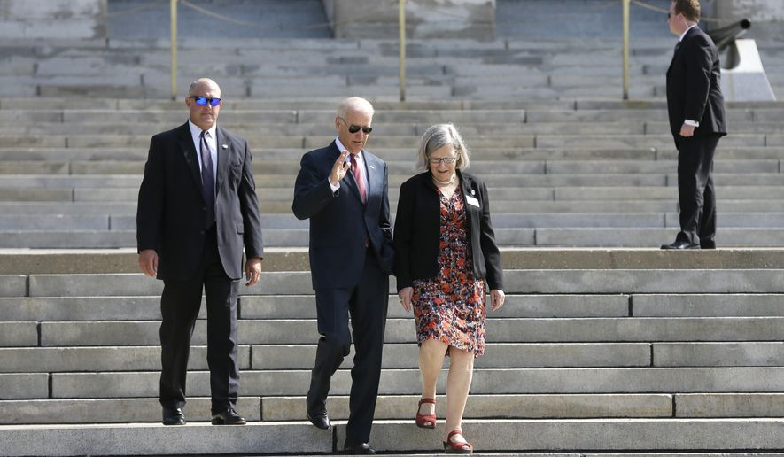 Vice President Joe Biden walks with Sister Simone Campbell, right, before the kickoff of the Nuns on the Bus tour, Wednesday, Sept. 17, 2014, at the Statehouse in Des Moines, Iowa. (AP Photo/Charlie Neibergall)