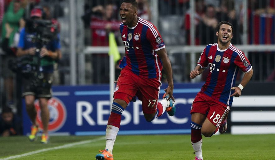 Bayern's Jerome Boateng, left, celebrates after he scored his side first goal during the Champions League Group E soccer match between FC Bayern Munich and Manchester City at Allianz Arena in Munich, southern Germany, Wednesday Sept. 17, 2014. Right are Bayern's Juan Bernat. (AP Photo/Matthias Schrader)