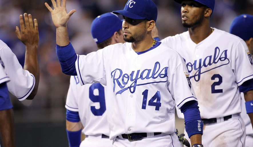 Kansas City Royals' Omar Infante (14) and Alcides Escobar (2) are congratulated at the end of a baseball game against the Chicago White Sox at Kauffman Stadium in Kansas City, Mo., Wednesday, Sept. 17, 2014. The Royals won 6-2. (AP Photo/Colin E. Braley)