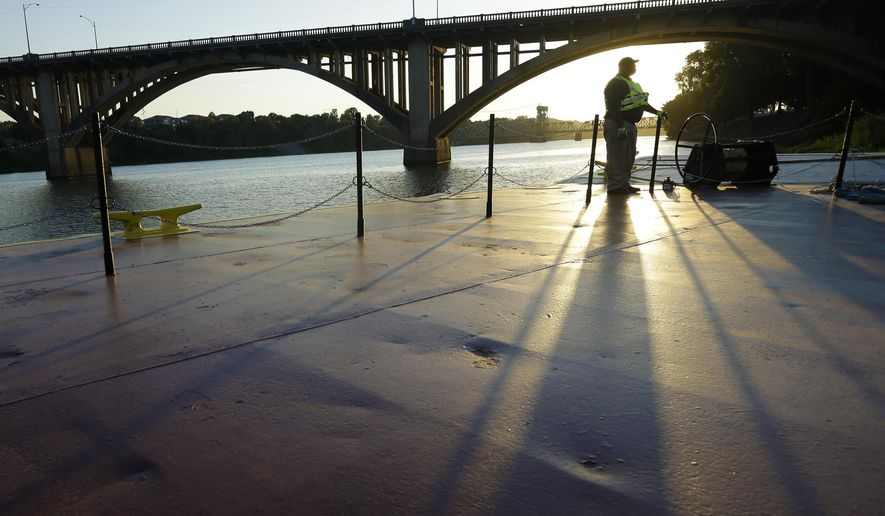 "In this Aug. 13, 2014 photo, a crew member of the U.S. Army towboat ""Mississippi"" waits on a barge as it is maneuvered to the shore on the Arkansas River near the Broadway Street Bridge at North Little Rock, Ark. A Missouri construction company has submitted the lowest bid to replace 1923 bridge. (AP Photo/Danny Johnston)"