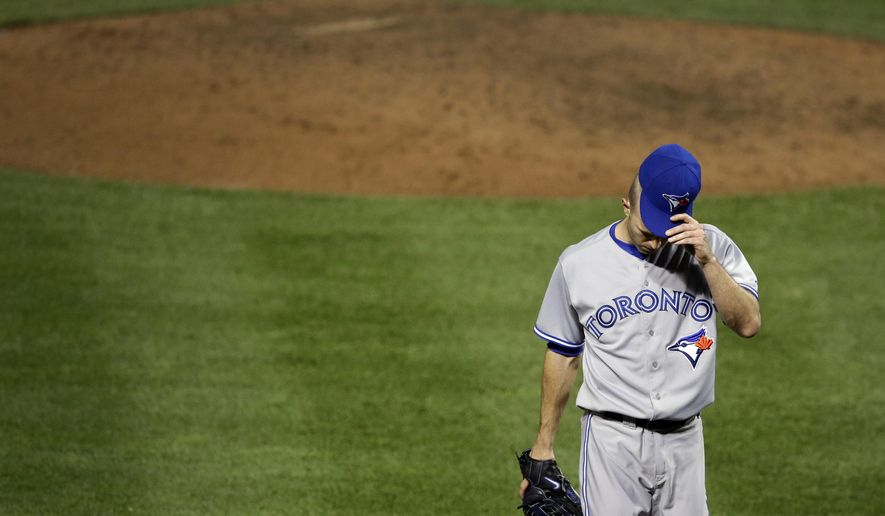 Toronto Blue Jays starting pitcher J.A. Happ adjusts his cap as he walks off the field after the fifth inning of a baseball game against the Baltimore Orioles, Wednesday, Sept. 17, 2014, in Baltimore. Baltimore's Steve Pearce hit a three-run home run in the fifth, and Baltimore won 6-1. (AP Photo/Patrick Semansky)