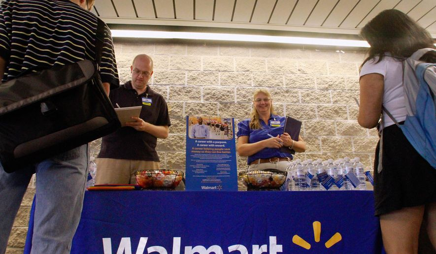 FILE - In this Thursday, Sept. 1, 2011, photo, Wal-Mart employees Jon Christians and Lori Harris take job applications and answers questions during a job fair at the University of Illinois Springfield campus in Springfield, Ill. Wal-Mart Stores Inc. says it plans to hire 60,000 temporary holiday workers for the crucial holiday season in 2014, an increase of nearly 10 percent from last year. (AP Photo/Seth Perlman, File)