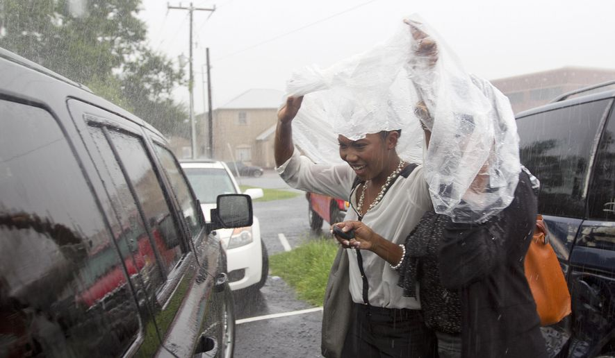 Women use a plastic sheet to try and stay dry in downtown Conroe, Texas, Thursday, Sept. 18, 2014. Heavy rains continue to hit the region with several power outages reported in the downtown area and continuing west toward Lake Conroe. (AP Photo/ The Courier, Jason Fochtman)