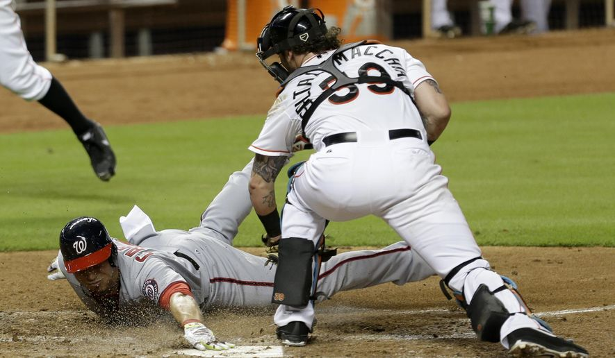 Washington Nationals' Asdrubal Cabrera (3) slides safely into home plate as Miami Marlins catcher Jarrod Saltalamacchia (39) is late on the tag in the fourth inning of a baseball game in Miami, Thursday, Sept. 18, 2014. Cabrera scored on a base hit by Kevin Frandsen. (AP Photo/Alan Diaz)