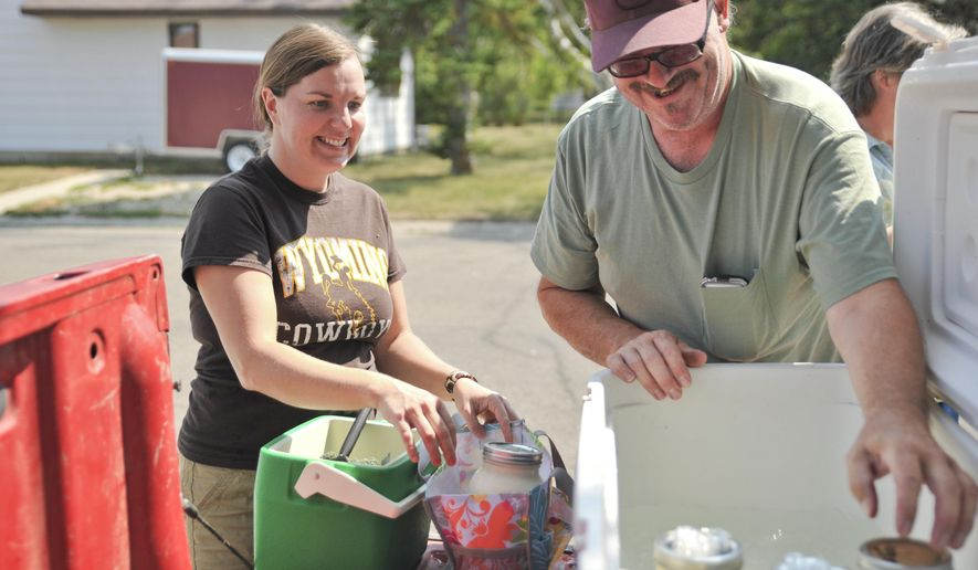 Sarah Mercer holds open her bag as Frank Wallis of Recluse, Wyo., pulls out jars of non-processed whole milk for her Friday, Aug. 8, 2014 near the Sheridan County Fairgrounds in Sheridan, Wyo. (AP Photo/The Sheridan Press, Justin Sheely)