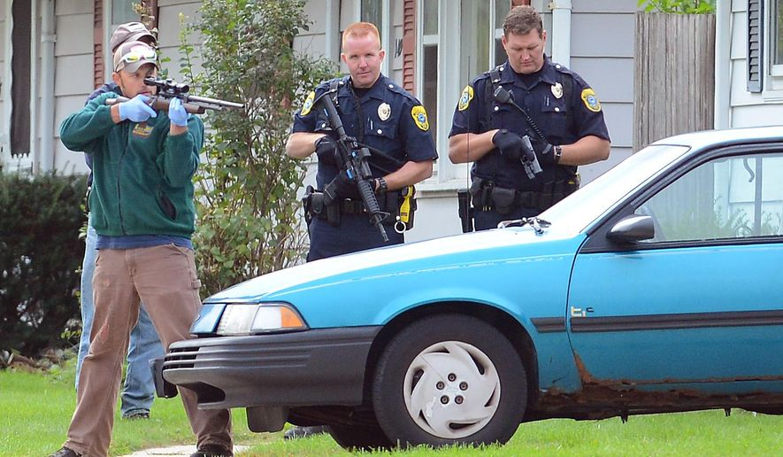 A Wisconsin DNR worker holding a tranquilizer gun, left, and heavily armed Green Bay police officers stand guard near where a bear was contained in a yard off Shawano Avenue, in Green Bay, Wis., Sept. 18, 2014.  (AP Photo/The Green Bay Press-Gazette, Jim Matthews)