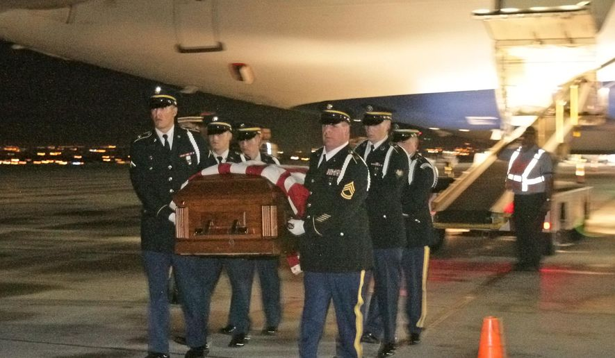 The remains of WWII casualty Montana Airman 1st Lt. William D. Bernier  are carried from a Delta plane by a Honor Guard in Billings, MT Wednesday Sept. 17, 2014. Bernier will be buried in Augusta Saturday. (AP Photo/The Gazette, Bob Zellar)