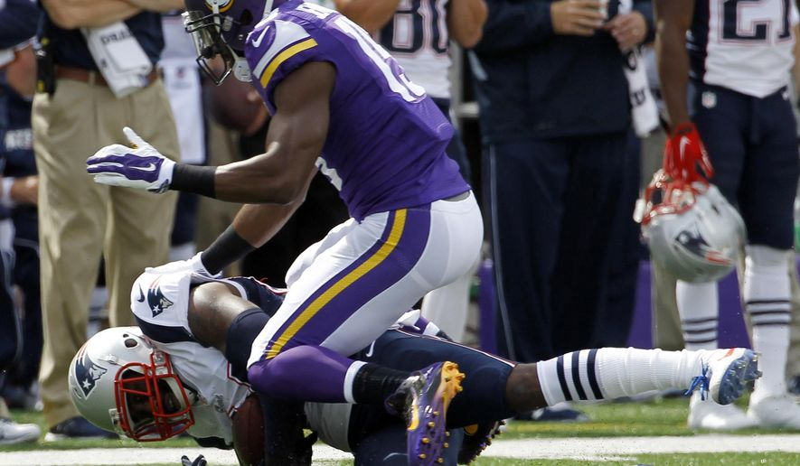New England Patriots cornerback Darrelle Revis, bottom, falls to the turf after intercepting a pass intended for Minnesota Vikings wide receiver Greg Jennings, top, during the second quarter of an NFL football game Sunday, Sept. 14, 2014, in Minneapolis. (AP Photo/Ann Heisenfelt)