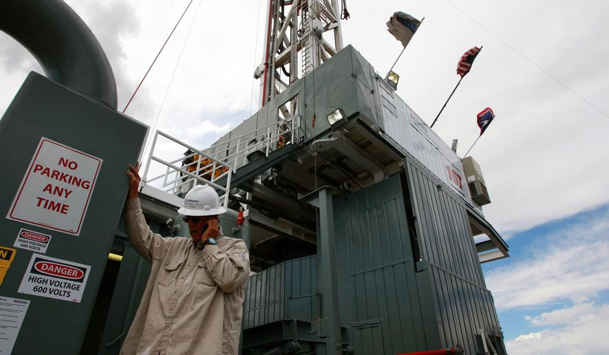 Tommy Hilliard, a company man for Jonah Energy, talks on the phone below the Ensign drilling rig he oversees Monday, Sept. 8, 2014 in the Jonah Field near Pinedale, Wyo. Jonah Energy recently acquired Encana's natural gas assets in the area. (AP Photo/Casper Star-Tribune, Alan Rogers)