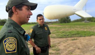 Assistant patrol agent in charge Lee Allbee, right, talks about the aerostat used by Border Patrol to look for smugglers and illegal crossings in the Rio Grande Valley,  Friday Sept. 5, 2014 at Penitas, Texas.  Since last November, the Border Patrol has stationed five surveillance sky cameras in the Rio Grande Valley area _ one in Penitas, two near Rio Grande City and two near Falfurrias, said agency spokesman Joe Gutierrez Jr.  (AP Photo/The Monitor, Gabe Hernandez)  MAGS OUT; TV OUT
