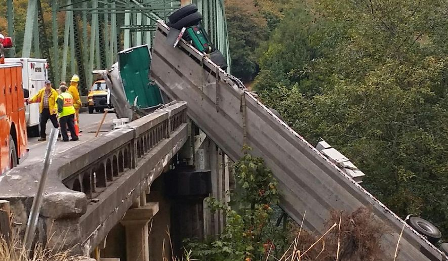 This photo provided by the Oregon State Police shows a truck hanging over the bridge. An Oregon State Police spokesman said the truck driver has been cited after a commercial truck hauling lumber products crashed at an Umpqua River bridge in southern Oregon, leaving the truck and trailer hanging over the bridge railing above the waterway. Lt. Gregg Hastings says an estimated 100 gallons of diesel leaked into the river Thursday, Sept. 18, 2014.  (AP Photo/Oregon State Police)