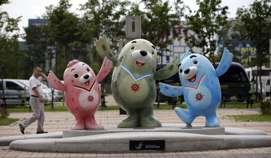 A man walks by dolls of the three official mascots, from left, Chumuro, Vichuon and Barame, of the the 2014 Incheon Asian Games in Incheon, west of Seoul, South Korea, Wednesday, Sept. 17, 2014. The games will be held in the South Korea's west city from Sept. 19 to Oct. 4. (AP Photo/Lee Jin-man)