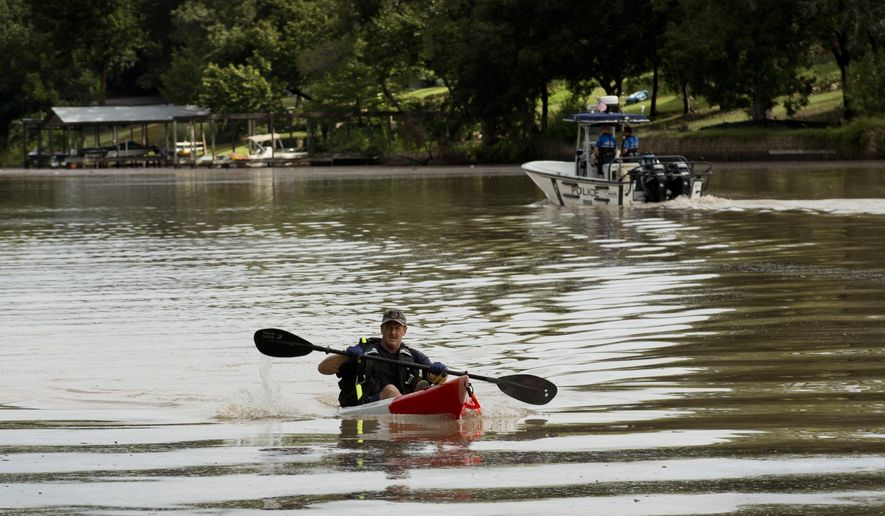 Austin Fire Department Capt. Scott Bartell searches Lake Austin for a missing Travis County Sheriff deputy who was swept away in a flood near Fritz Hughes Park in Austin, Texas on Thursday, Sept. 18, 2014. (AP Photo/Austin American-Statesman, Jay Janner)