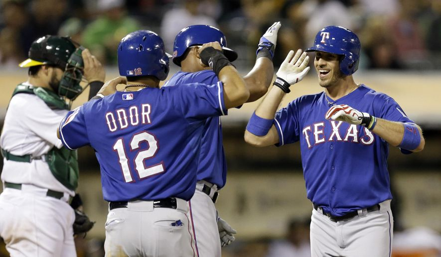 Texas Rangers' J.P. Arencibia, right, is congratulated by Adrian Beltre, center, and Rougned Odor (12) after Arencibia hit a three run home run off Oakland Athletics' Sean Doolittle in the ninth inning of a baseball game Wednesday, Sept. 17, 2014, in Oakland, Calif. (AP Photo/Ben Margot)