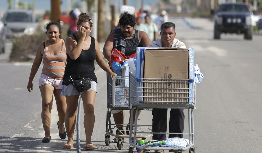 People carry looted goods taken from Walmart in Cabo San Lucas , Mexico,  Wednesday, Sept. 17, 2014.  Desperate locals and tourists were in survival mode in the resort area of Los Cabos on Wednesday, with electrical and water service still out three days after Hurricane Odile made landfall as a monster Category 3 storm. Looters stripped supermarkets of their food and other products, with some people fighting over goods. (AP Photo/Victor R. Caivano)