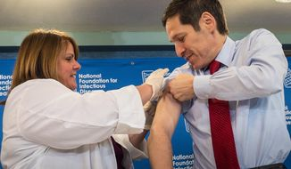 Dr. Thomas Frieden, director of the Centers for Disease Control and Prevention (CDC), receives a flu shot from Sharon Bonadies at the conclusion of a news conference at the National Press Club in Washington. (AP Photo/J. David Ake/File)