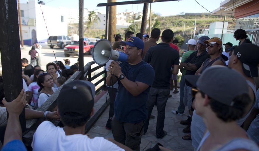 A man uses a bullhorn to call on residents to prepare themselves against looters and criminal gangs after the passing of Hurricane Odile in San Jose de los Cabos, Mexico, Wednesday, Sept. 17, 2014. Federal police on Thursday vowed to crack down on lawlessness and restore order in the hurricane-stricken resort area. There were reports of gunfire overnight, and residents in Los Cabos lit large bonfires to try to protect their neighborhoods as they faced a fourth day without power or running water following the blow from Hurricane Odile. (AP Photo/Dario Lopez-Mills)