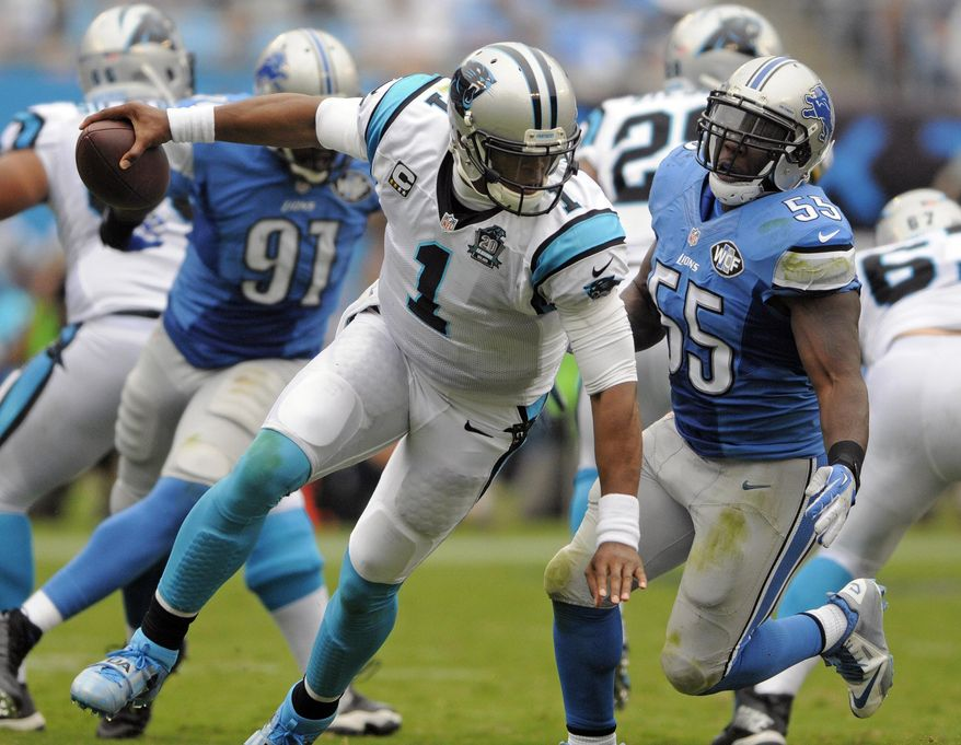 Carolina Panthers' Cam Newton (1) tries to escape Detroit Lions' Stephen Tulloch (55) during the second half of an NFL football game in Charlotte, N.C., Sunday, Sept. 14, 2014. (AP Photo/Mike McCarn)