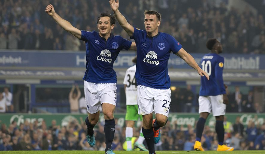 Everton's Seamus Coleman, centre right, celebrates alongside teammate Leighton Baines after scoring against Wolfsburg during their Europa League Group H soccer match at Goodison Park Stadium, Liverpool, England, Thursday Sept. 18, 2014. (AP Photo/Jon Super)