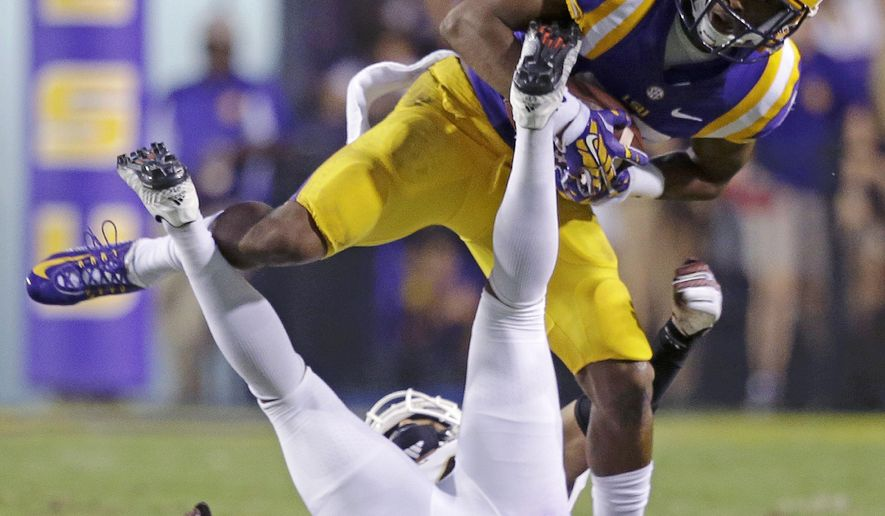 LSU wide receiver Travin Dural (83) pills in a a reception over Louisiana-Monroe cornerback Trey Caldwell in the second half of an NCAA college football game in Baton Rouge, La., Saturday, Sept. 13, 2014. LSU won 31-0. (AP Photo/Gerald Herbert)