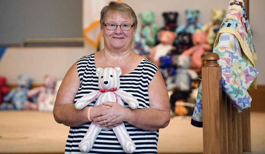 In this Sept. 2, 2014 photo, Susie Arwine holds one of the many teddy bears she made at the Kansas Christian Church in Kansas, Ill. Making teddy bears for those in need of good cheer has become a passion for Arwine. She and four other women are set to go on a mission trip to eastern Kentucky in Appalachia to personally give the bears and other handicrafts to families in financial need. (AP Photo/Journal Gazette, Kevin Kilhoffer)