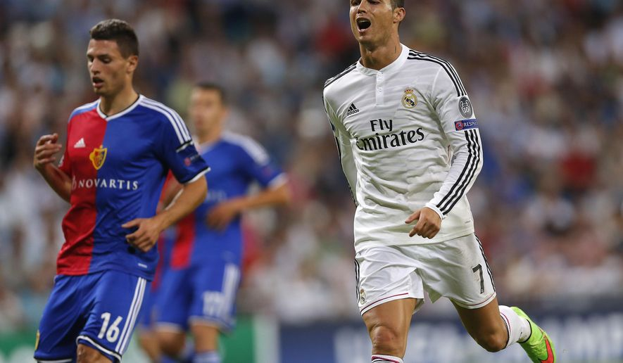 Real Madrid's Cristiano Ronaldo, right, reacts after missing a chance during the Champions League Group B soccer match between Real Madrid and Basel at the Santiago Bernabeu stadium in Madrid, Spain, Tuesday Sept. 16, 2014. (AP Photo/Daniel Ochoa de Olza)