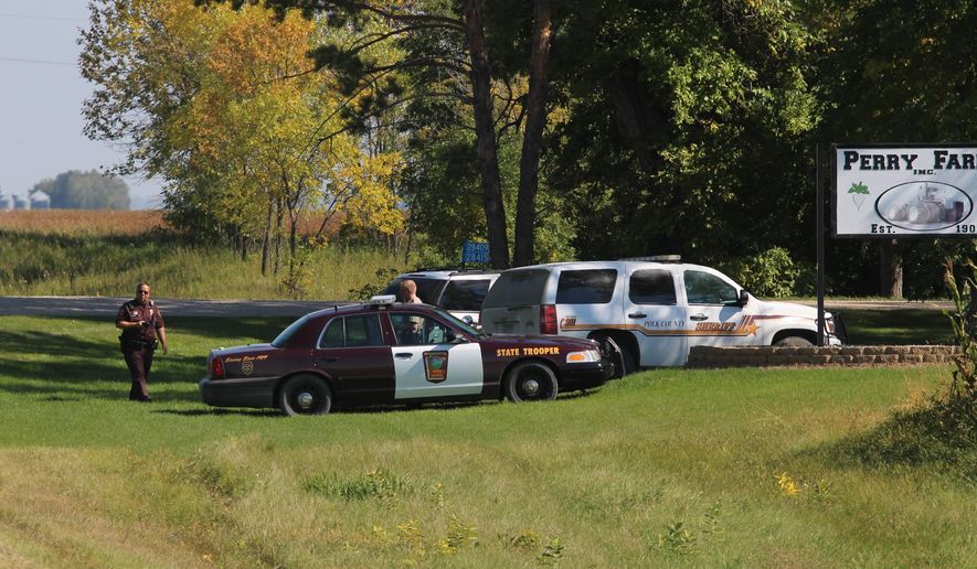 Multiple law enforcement vehicles and law enforcement officers converge on Perry Farms south of Crookston, Minn., Thursday, Sept. 18, 2014. Authorities say a northwestern Minnesota sheriff's deputy and a suspect are wounded after an officer-involved shooting. The Minnesota Bureau of Criminal Apprehension says the shooting happened Thursday in rural Crookston in Polk County. A Polk County sheriff's deputy and the suspect are being treated for non-life-threatening injuries. (AP Photo/The Daily Times, Derek Martin)