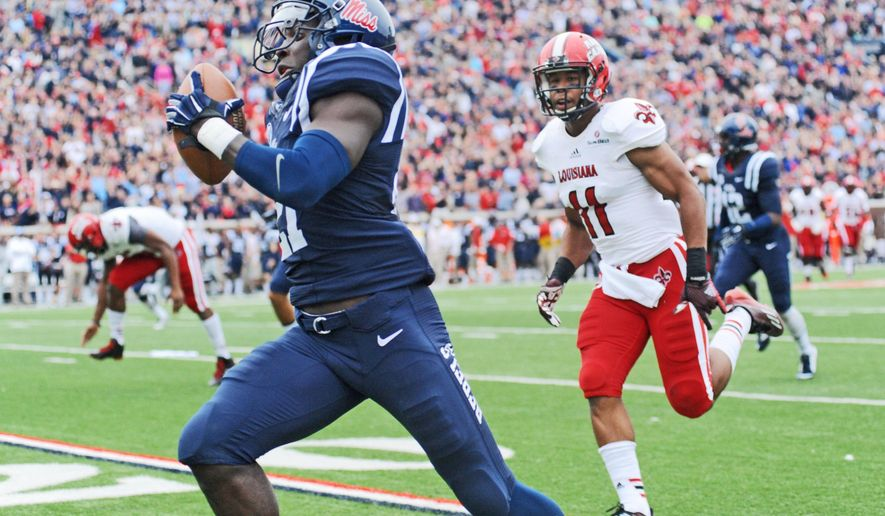 Mississippi defensive back Senquez Golson (21) returns an interception for a touchdown as Louisiana-Lafayette wide receiver James Butler (11) chases at Vaught-Hemingway Stadium in Oxford, Miss. on Saturday, Sept. 13, 2014. Mississippi won 56-15. (AP Photo/Oxford Eagle, Bruce Newman) MAGS OUT; NO SALES; MANDATORY CREDIT