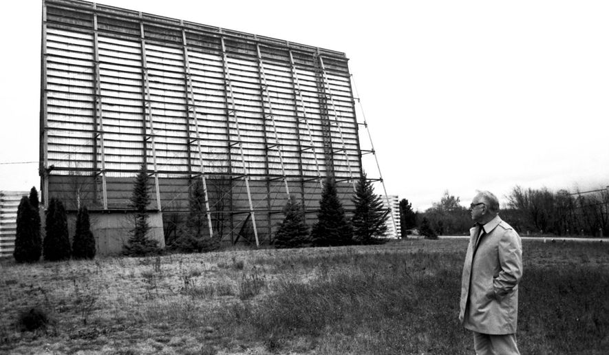 "ADVANCE FOR SUNDAY, SEPT. 21- In a fall 1987 file photo, Paul Florence, vice-president of the Drive-In Theater Corp., looks at the back side of the movie screen at the Airport Drive-In Theatre in Marquette, Mich., shortly before the Marquette County Board approved purchasing and razing the theatre. Plowed under by an ever-building wave of technology, Marquette County's once popular three outdoor theaters reside in what's known today as the drive-in theater ""graveyard."" (AP Photo/The Mining Journal)"