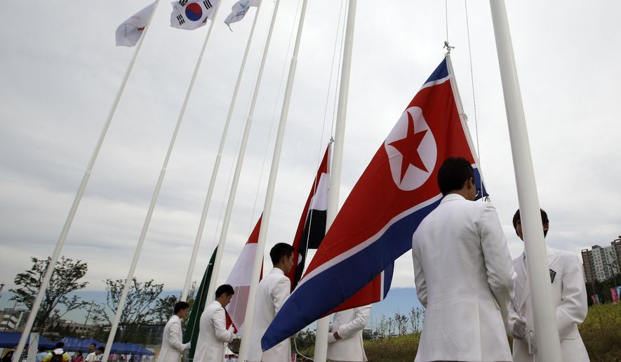 A North Korean flag, right, is prepared for a welcoming ceremony at the Flag Plaza of the Athlete's Village for the 2014 Incheon Asian Games in Incheon, west of Seoul, South Korea, Thursday, Sept. 18, 2014. The games will be held in the South Korea's west city from Sept. 19 to Oct. 4. (AP Photo/Lee Jin-man)