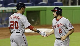 Washington Nationals Anthony Rendon (6) is congratulated by teammate Ian Desmond (20) after Rendon scored on a double by Wilson Ramos against the Miami Marlins in the fourth inning of a baseball game in Miami, Thursday, Sept. 18, 2014. (AP Photo/Alan Diaz)