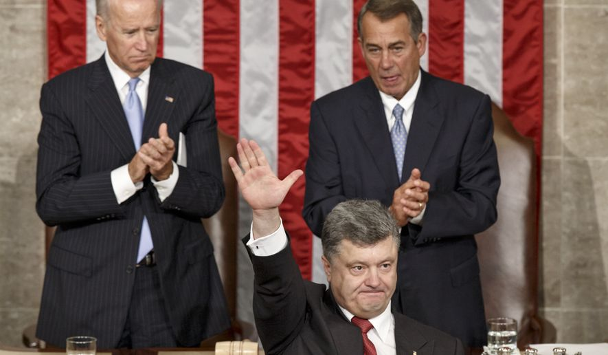 Ukrainian President Petro Poroshenko, joined by Speaker of the House John Boehner, R-Ohio, right, and Vice President Joe Biden, left,  waves after addressing a joint meeting of Congress, at the Capitol in Washington, Thursday, Sept. 18, 2014. Poroshenko is seeking more robust U.S military assistance to help his country in its fight against Russian-backed rebels and will also be meeting with President Barack Obama.  (AP Photo/J. Scott Applewhite)