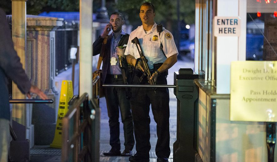 A Secret Service police officer holds a weapon as he stands near an entrance to the White House complex during an evacuation minutes after President Barack Obama departed Washington for Camp David aboard Marine One on Friday, Sept. 19, 2014. A Secret Service agent at the scene says someone jumped the fence surrounding the White House. (AP Photo/Evan Vucci)