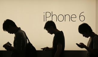 People wait to buy the new Apple iPhone 6 and 6 Plus devices, outside an Apple store in Hong Kong Friday morning, Sept. 19, 2014. (AP Photo/Vincent Yu) ** FILE **