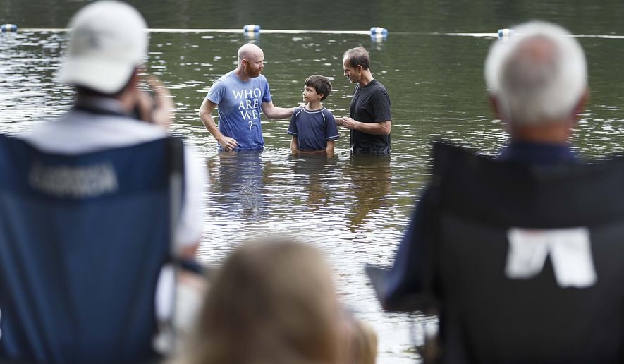 In this Sunday, Aug. 24, 2014 photo, in background, pastors Marshall Benbow, left, and Bill Goans, right, baptize Benjamin Huitt at Lynwood Lakes, in Greensboro, N.C. Once a year, Grace Community Church performs their baptisms outside. (AP Photo/News & Record, Lynn Hey)