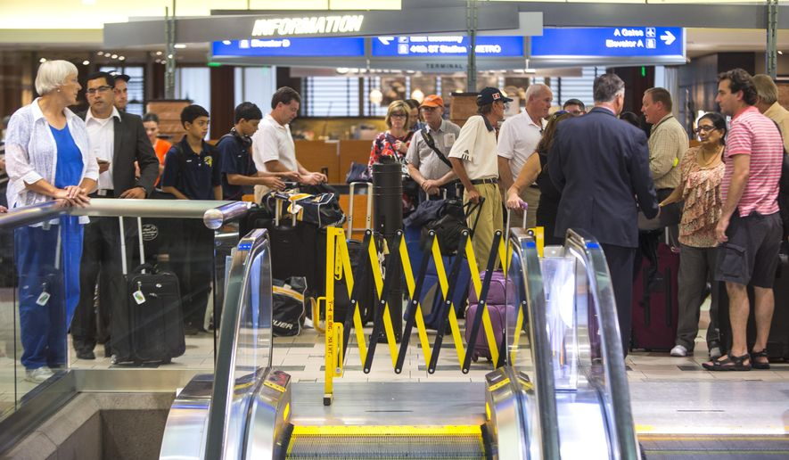 Hundreds of travelers at Phoenix Sky Harbor International Airport's terminal 4 wait for police to search for an armed suspect, Thursday, Sept. 18, 2014. The suspect is believed to be involved in a Tempe shooting. (AP Photo/The Arizona Republic, Charlie Leight)