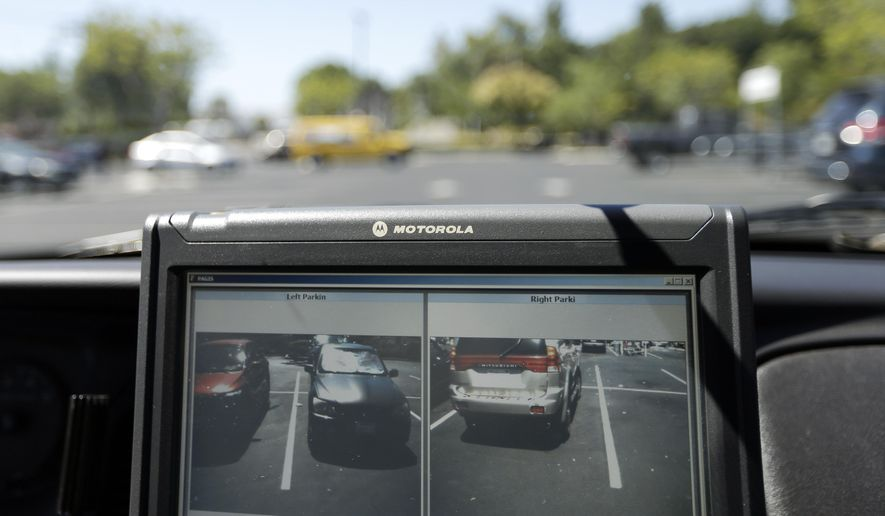A police vehicle driven by San Diego County Deputy Sheriff Ben Chassen reads the license plates of cars in a parking lot Wednesday, Sept. 17, 2014, in San Marcos, Calif. Facing a heroin epidemic, Maryland officials will spend $120,000 to buy license-plate readers to check the tags of cars coming into Ocean City, believing it can help halt some of the drugs flowing to the Eastern Shore, which has been particularly hard-hit.  (AP Photo/Gregory Bull) **FILE**