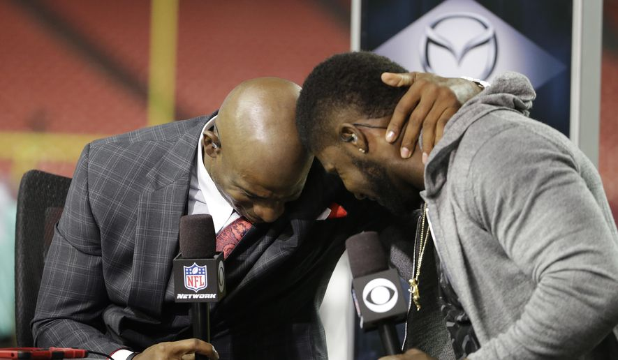 NFL Network broadcaster and former NFL football player Deion Sanders, left, embraces Atlanta Falcons wide receiver Devin Hester after the second half of an NFL football game, Thursday, Sept. 18, 2014, in Atlanta. The Atlanta Falcons won 56-14. (AP Photo/David Goldman)