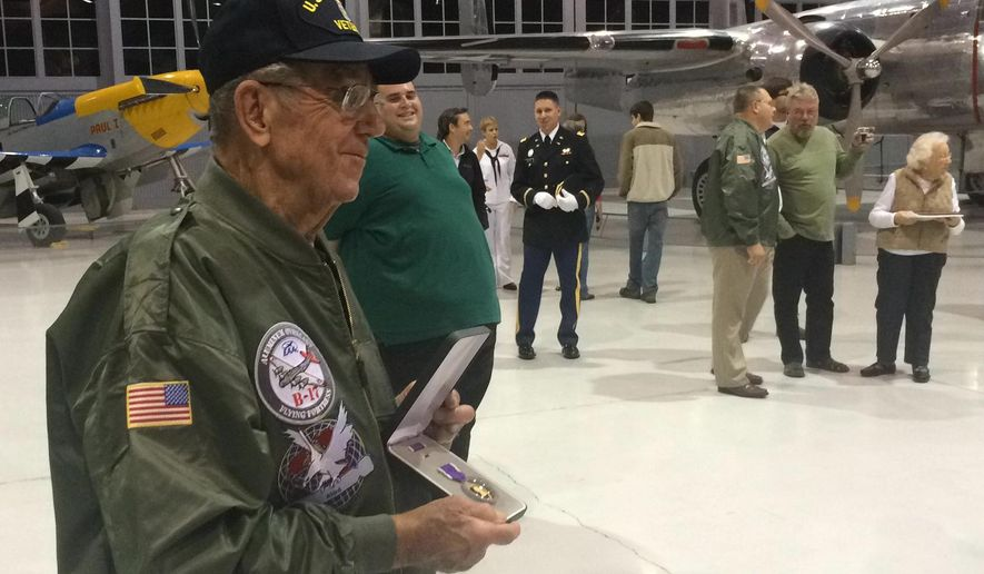 Fred Zurbuchen, 89, of Waupun poses for family pictures Thursday, Sept. 18, 2014, with his Purple Heart in the Eagle Hangar of the Experimental Aircraft Association AirVenture Museum in Oshkosh. Zurbuchen, who was a staff sergeant in the 8th Air Force during World War II, was injured Sept. 9, 1944, while flying his 10th of 25 missions as a B-17 ball turret gunner. After a fire destroyed his paper work shortly after the war, Zurbuchen tried everything he could to get his medal with no success. On Thursday, representatives of EAA and the U.S. Army surprised Zurbuchen with a ceremony to present him with the honor. (AP Photo/The Oshkosh Northwestern, Nathaniel Shuda)