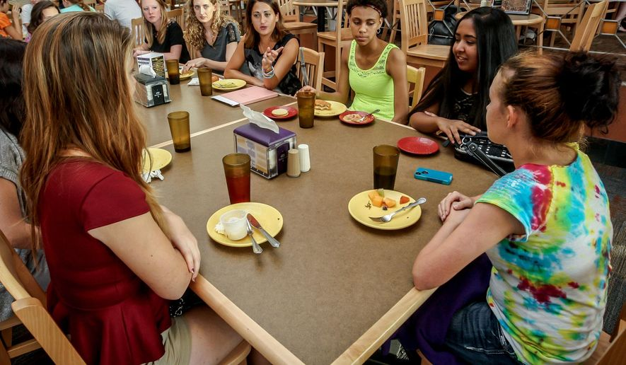 ADVANCE FOR RELEASE MONDAY, SEPT. 22, 2014, AND THEREAFTER- In this Sept. 11, 2014 photo, Danielle Gletow, founder of One Simple Wish, fourth from right, sits down with teens to talk with them about life experiences at East Carolina University, in Greenville, N.C. (AP Photo/The Daily Reflector, Will Stricklin)